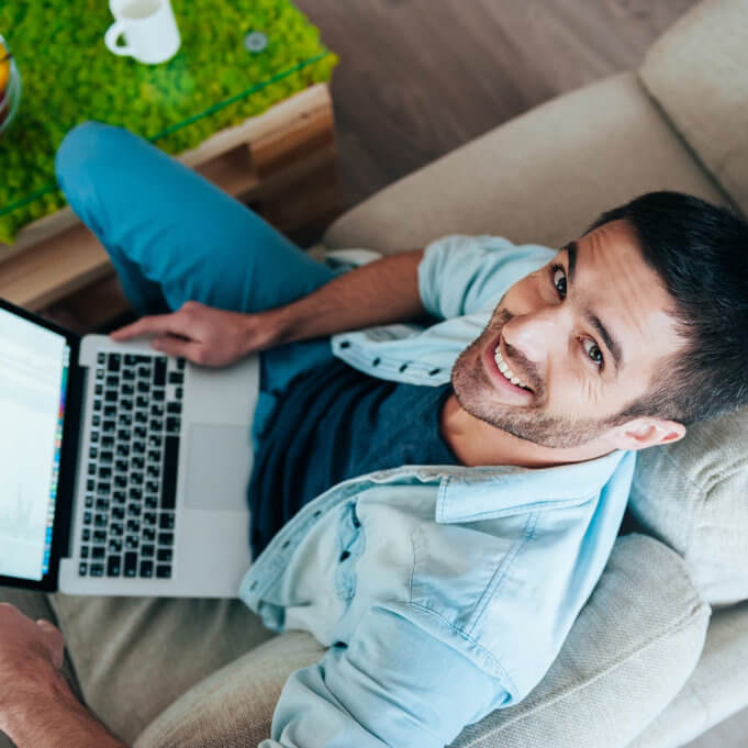 Top view of handsome young man working on laptop and smiling while sitting on the couch at home